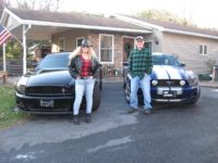 Man and women standing in front of two Mustang cars