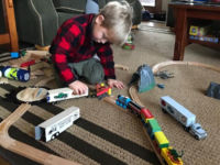 Boy playing with wooden train set