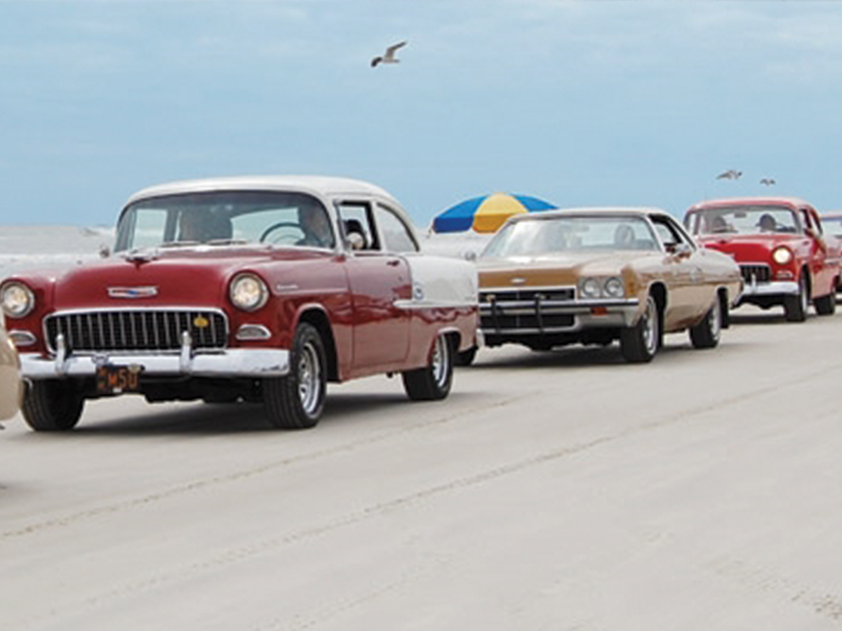 vintage chevrolet cars driving at the beach